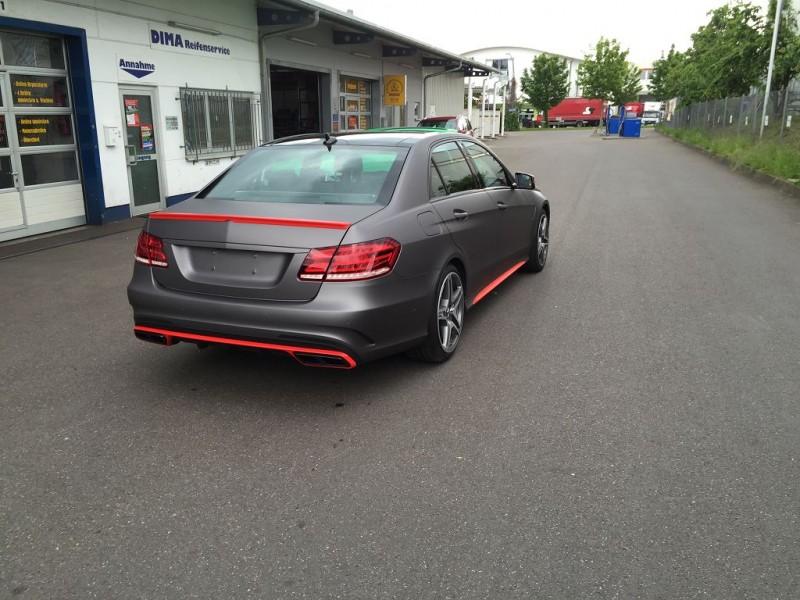 Heckansicht auf einen Mercedes E63 AMG S mit Komplettfolierung in Anthrazit Metallic Matt und Akzenten in HotRod Red glänzend