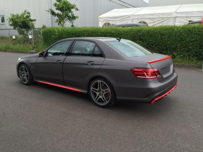 Seitliche linke Ansicht auf einen Mercedes E63 AMG S mit Komplettfolierung in Anthrazit Metallic Matt und Akzenten in HotRod Red glänzend