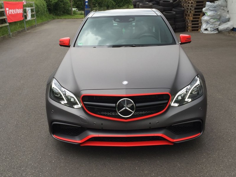 Frontansicht auf einen Mercedes E63 AMG S mit Komplettfolierung in Anthrazit Metallic Matt und Akzenten in HotRod Red glänzend
