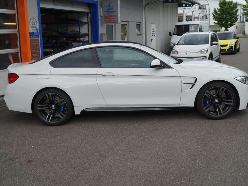 Rechte, volle Seitenansicht eines BMW M4 nach Teilfolierung mit Dekorstreifen