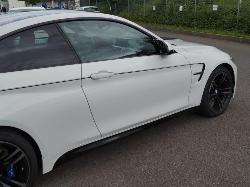 Rechte Seitenansicht eines BMW M4 nach Teilfolierung mit Dekorstreifen