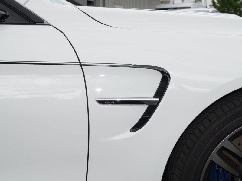Nahaufnahme Markenschriftzug eines BMW M4 nach Teilfolierung