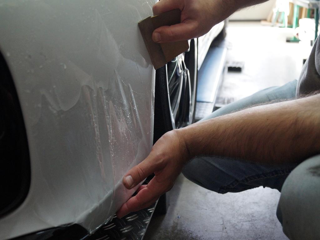 Mitarbeiter von Sticker-Wekr bringt unsichtbare Lackschutzfolie an Porsche an